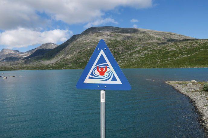 «Strømvirvel, dykket tappeløp, inntak». Dette skiltet snur mot land, padlere kan derfor ikke se denne advarselen. Her er det trolig et undersjøisk vanninntak et sted, men det er ikke mulig å se hvor hen.